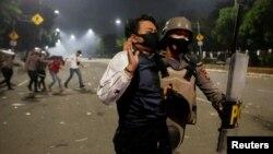 Seorang polisi menahan seorang demonstran dalam unjuk rasa menentang UU Cipta Karya di Jakarta, 8 Oktober 2020. (Foto: Reuters)