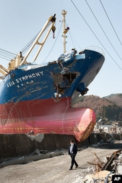 A man walks past a huge ship that breached a seawall in Kamaichi, Japan