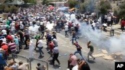 Warga Palestina menghindari gas air mata yang ditembakkan oleh polisi Israel di kota tua Yerusalem (21/7).