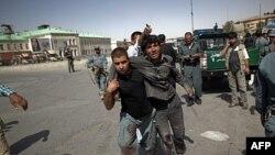 Avganistanski policajac pomaže ranjeniku da se skloni posle napada na policijsku stanicu u Kabulu