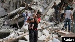 敘利亞阿勒頗由非政府組織控制的街區2016年9月21日遭空襲,一名男子在空襲後抱著一名受傷的兒童。
