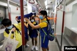 """香港小学生在""""全民国家安全教育日""""会场内手持模仿机关枪在一个布置成地铁车厢的展览内游玩"""