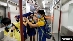 """香港小學生在""""全民國家安全教育日""""會場內手持模仿機關槍在一個佈置成地鐵車廂的展覽內遊玩 (路透社照片)"""