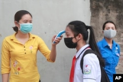 A student is scanned for temperature before entering Dinh Cong secondary school in Hanoi, Vietnam Monday, May 4, 2020.