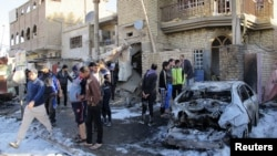 Residents gather at the site of a car bomb attack in the Hurriya district in Baghdad, January 10, 2013.