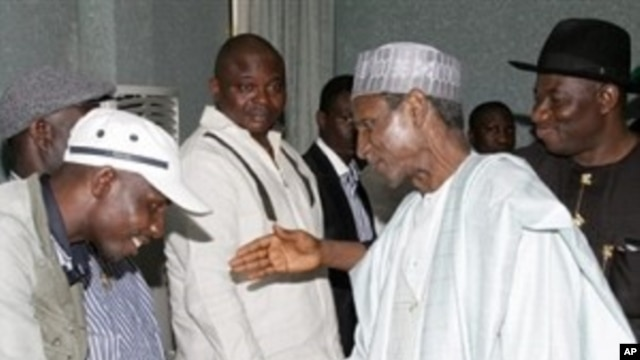 Nigerian President Umaru Yar'Adua (C), flanked by Vice President of Nigeria, Jonathan Goodluck (R), shakes hands with Government Ekpemupolo (L), commander of rebel group MEND, during their meeting in Abuja (File Photo)