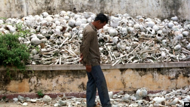 A Cambodian man walks past one of the many killing fields sites at a school on the outskirts of Phnom Penh.