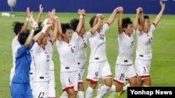 21일 한국 서울 월드컵경기장에서 열린 2013 동아시안컵 여자부 한국과 북한의 경기 후, 승리한 북한 선수들이 관중들에게 인사하고 있다.