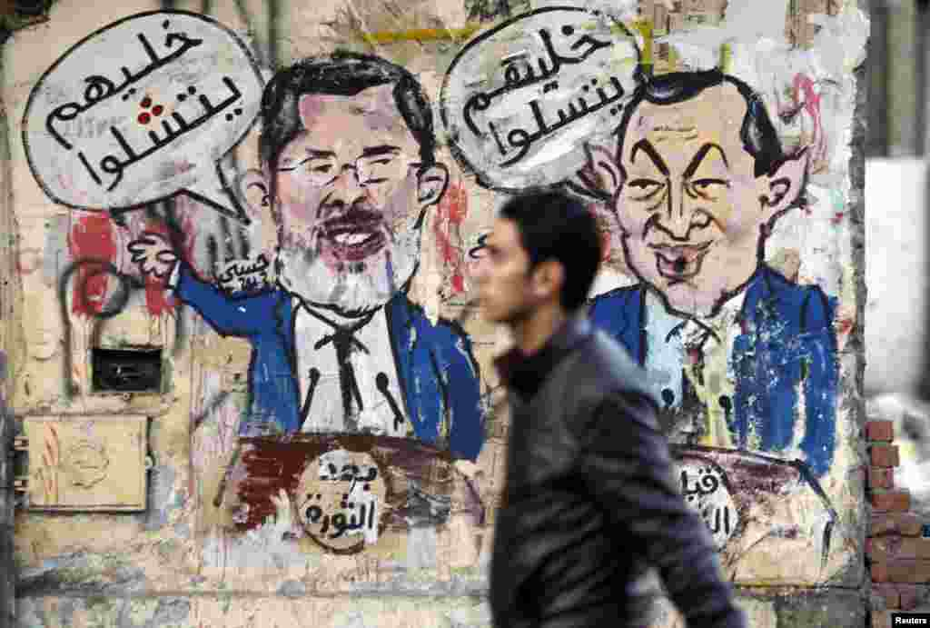 "A protester walks past a graffiti during a march at Tahrir Square in Cairo. The march, was organized by Egyptians who oppose President Mohamed Morsi and members of the ruling Muslim Brotherhood on the second anniversary of the resignation of President Mubarak. The arabic words read, ""After the revolution - let them speak"" (L), ""Before the revolution - let them play"" (R)."