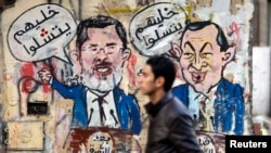 A protester walks past a graffiti during a march at Tahrir Square in Cairo, February 11, 2013. The march, was organized by Egyptians who oppose Egypt's President Mohamed Morsi and members of the ruling Muslim Brotherhood on the second anniversary of the r