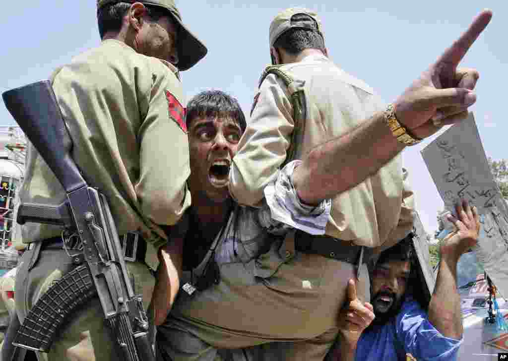 Kashmiri protesters shout slogans against Israel from inside a police vehicle after they were detained during a protest in Srinagar, India, July 14, 2014.