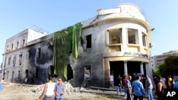 People gather to look at the site of a car bombing in Benghazi, Libya, September 11, 2013.