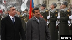 Armenian President Serzh Sargsyan (L) walks with Iran's President Mahmoud Ahmadinejad (C) during an official welcoming ceremony in Yerevan, Dec. 23, 2011.