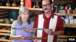 Donor Steven Martin and University of Idaho curator Priscilla Wegars hold antique opium pipes. (VOA/T. Banse)