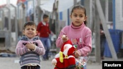 Displaced Christian children, who fled Islamic State, carry gifts given to them at Zayuna camp in Baghdad, Iraq, Dec. 23, 2015.