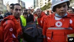 Nhân viên hội Chữ Thập đỏ khiêng thi hài nạn nhân từ địa điểm nổ bom. Vụ nổ bom xảy ra trong trung tâm thủ đô Beirut của Li Băng, 27/12/13