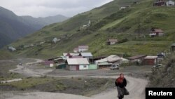 A woman walks along a road in the settlement of Akhty in southern Dagestan, July 4, 2012