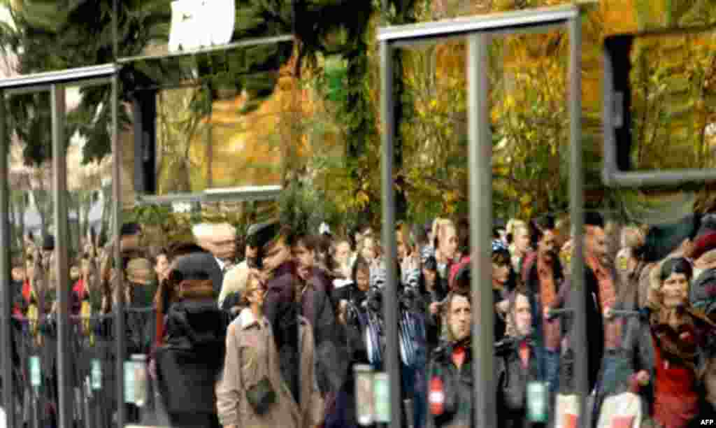 Romanian Orthodox worshippers are reflected in a bus window, as they wait in long lines to touch the remains of Saint Mina or Menas, in Bucharest, Romania, Thursday, Nov. 11, 2010. Thousands wait long hours to touch the remains of the saint who, according