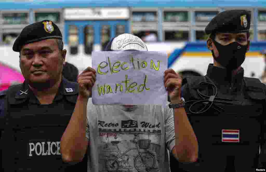 A demonstrator holds up a sign during a protest against military rule at the Victory Monument in Bangkok, May 27, 2014.