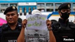 Seorang demonstran memegang kertas bertuliskan pesan saat bergabung dengan demonstran lainnya yang berunjuk rasa menentang aturan militia di monument Kemenangan (Victory Monument) di Bangkok (27/5).
