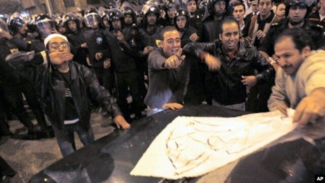 Egyptian Christians cheer as they put a piece of paper that reads 'we don't need Habib El-Adly, Minister of the Interior' on a car driven by a Christian during clashes with riot police outside al-Abasseya Cathedral in Cairo late night, 02 Jan 2011.