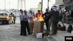 伊拉克失业劳工一大早在巴格达街头烤火取暖,等待有人聘用他们做短工。