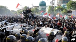 Riot police officers block students from advancing toward the local parliament during a rally in Surabaya, East Java, Indonesia, Sept. 26, 2019.