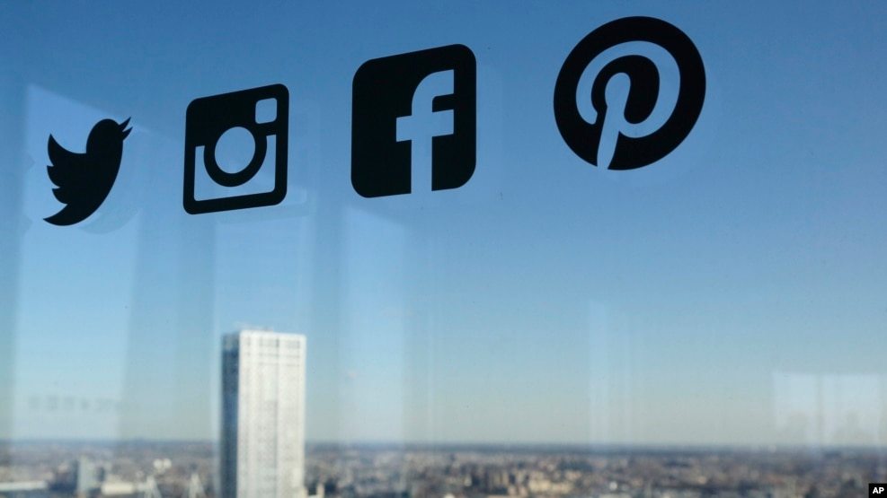 FILE - Icons for Twitter, Instagram, Facebook and Pinterest are displayed on a window in New York, Jan. 13, 2016.