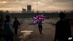 """Un homme court avec le drapeau anglais dans le camp pour migrants appelé """"la jungle"""" près Calais, France, le 25 octobre 2016."""