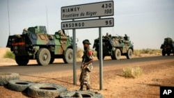 FILE - French armored vehicles head toward the Niger border before making a left turn north in Gao, northern Mali.