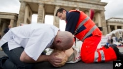 Paramedics demonstrate how to apply CPR on a dummy in front of Brandenburg Gate in Berlin.