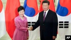 中国国家主席习近平(右)在北京人大会堂与前来参观北京阅兵仪式的韩国总统朴槿惠握手。(2015年9月2日)