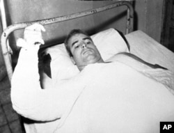 FILE - U.S. Navy Lt. Cmdr. John S. McCain lies injured in North Vietnam wearing an arm cast, in this undated photo.