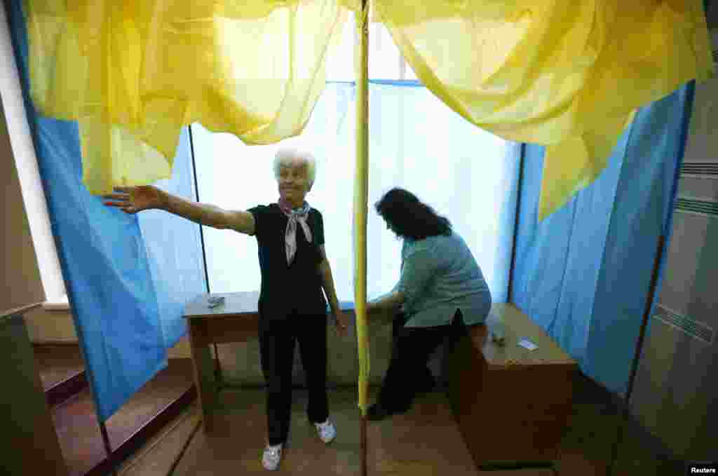 Election commission workers adjust a voting booth at a polling station in Kyiv, May 24, 2014.