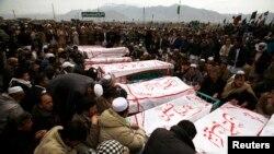 Người Hồi giáo Shia ngồi cạnh quan tài các nạn nhân bị giết chết trong vụ nổ bom ở Quetta.
