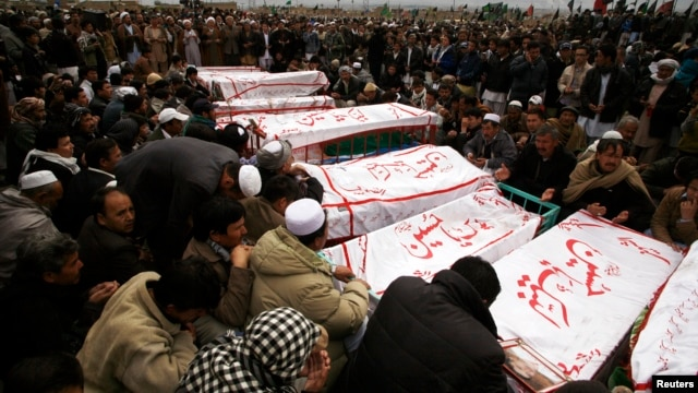 Shi'ite Muslims sit around coffins of victims killed in Saturday's bomb attack, during a funeral at a cemetery in Quetta, February 20, 2013.