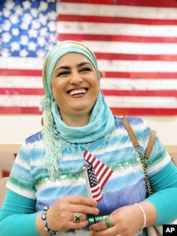 This September 2019 provided by Danielle Luna shows Iraqi born refugee Nada Al Rubaye at her naturalization ceremony in Phoenix. The artist left Baghdad after one of her sons and several other relatives were killed in the widespread violence.