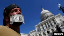 在國會山前一名聯邦僱員用美元將自己的咀封上﹐抗議政府關門。