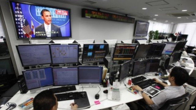 Employees of a foreign exchange firm monitor screens, with a television news reports that President Barack Obama announced US debt limit deal, in Tokyo, August 1, 2011