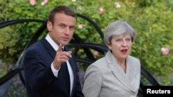 លោក Emmanuel Macron ប្រធានាធិបតីបារាំងអមដំណើរលោកស្រី Theresa May នាយករដ្ឋមន្ត្រីអង់គ្លេស ទៅកាន់សន្និសីទកាសែតនៅវិមាន Elysee ក្នុងក្រុងប៉ារីស ប្រទេសបារាំង កាលពីថ្ងៃទី១៣ ខែមិថុនា ឆ្នាំ២០១៧។