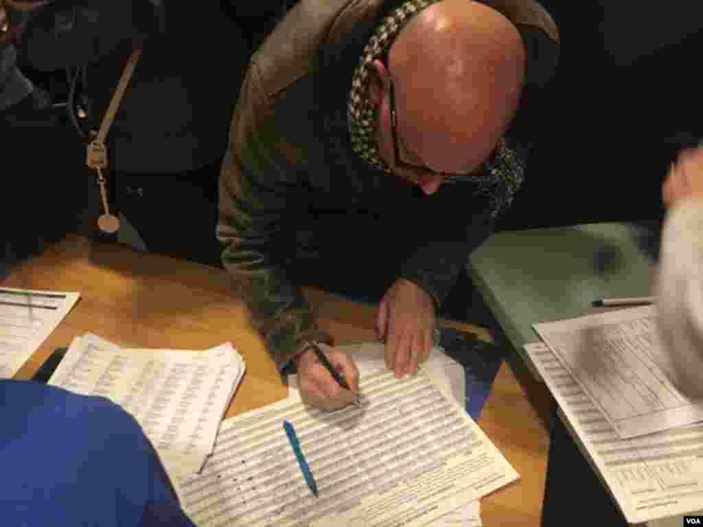 A caucus-goer registers at Hanawalt Elementary School, Des Moines, Iowa, Feb. 1, 2016. (M. Cagler/VOA)