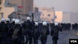 Polisi anti huru-hara Bahrain mengejar para demonstran anti-pemerintah di kawasan Muslim Shiah di Sitra, Bahrain (1/1).