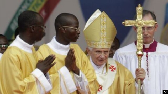 Pope Benedict XVI, second right, is accompanied by members of the clergy as he leaves following Sunday Mass, at the national stadium in Cotonou, Benin, November 20, 2011.