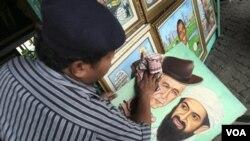 Pelukis S. Wito di studio pinggir jalannya, Senin (2/5) mengelap lukisannya yang menggambarkan Osama bin Laden dengan mantan Presiden AS George W. Bush.