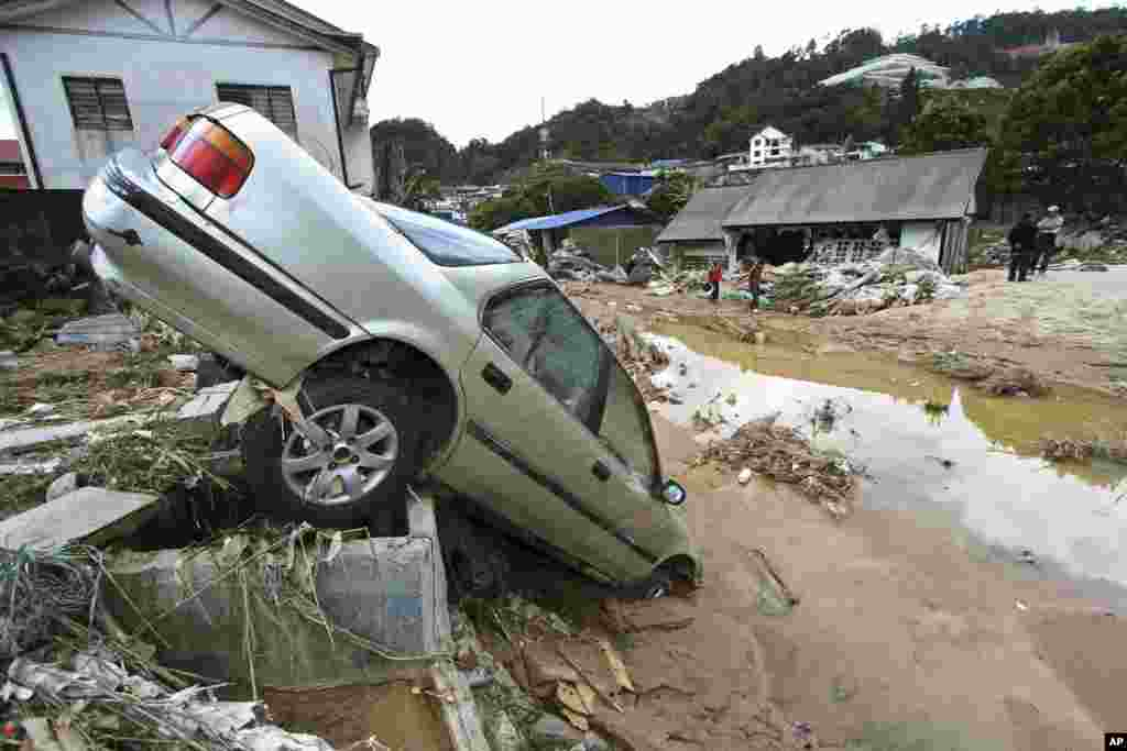 People stand near a car destroyed by a mud slide in Cameron Highlands, Malaysia. Several people were killed after water released from a dam caused a flash flood in the resort area, according to local sources.