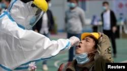 武汉一位医护人员正在对一名建筑工人采取进行核酸检测的样本。