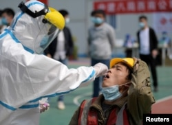 FILE PHOTO: A worker in a protective suit collects a swab from a construction worker for nucleic acid test in Wuhan, Hubei province, the epicentre of the novel coronavirus disease (COVID-19) outbreak in China, April 7, 2020.