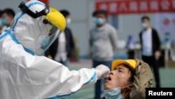武漢一位醫護人員正在對一名建築工人提取進行核酸檢測的樣本。