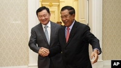 Former Thai Prime Minister Thaksin Shinawatra, left, is welcomed by Cambodian Prime Minister Hun Sen upon arrival at Peace Palace in Phnom Penh, Cambodia, September 17, 2011.