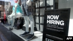 FILE - A now hiring sign is posted in the window of a clothing store in San Francisco, California.